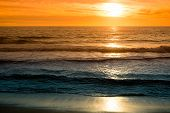 sunset on beach, orange and blue colors and waves
