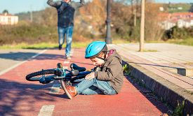 picture of screaming  - Boy in the street ground with a knee injury screaming after falling off to his bicycle - JPG