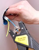 image of insulator  - Electrician insulating electric wires of an electric box - JPG