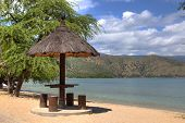 image of beach hut  - A natural leaf covered beach hut with wood stools in timor leste - JPG