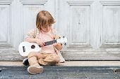 picture of ukulele  - Little happy boy plays his guitar or ukulele - JPG