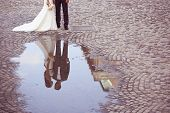 foto of paved road  - Bride and groom reflected in slop on paved road - JPG