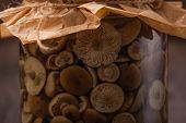 stock photo of marinade  - Marinaded mushrooms in a glass jar on wooden table - JPG