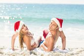 stock photo of beach hat  - happy couple with Christmas hat on the beach - JPG