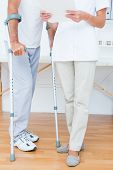 picture of crutch  - Doctor showing clipboard to her patient with crutch in medical office - JPG