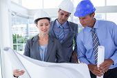 picture of hard_hat  - Businessmen and a woman with hard hats and holding blueprint in the office - JPG