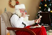 image of letters to santa claus  - Santa Claus sitting with children letters in comfortable chair near fireplace at home - JPG
