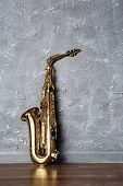 picture of saxophones  - Golden saxophone on gray wall background - JPG
