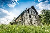 stock photo of abandoned house  - Abandoned wooden house surrounded by romantic nature - JPG