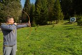 picture of longbow  - A man shoots a bow - JPG