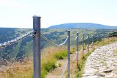 pic of mountain chain  - Closeup of metal safety chain on a mountain trail - JPG