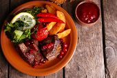 stock photo of deer meat  - Tasty roasted meat with cranberry sauce - JPG