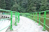 stock photo of dam  - Green bridge and dam water on a mountain trail - JPG