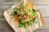stock photo of tacos  - Tasty taco with greens on paper on table close up - JPG