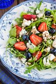 foto of pine nut  - Fresh delicious arugula strawberry blueberry pine nuts and blue cheese salad