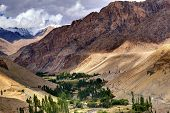 stock photo of gautama buddha  - Rocky landscape of Ladakh with green valley in the middle play of light and shadowJammu and Kashmir India - JPG