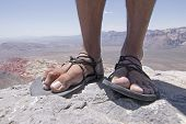picture of primitive  - Closeup of weathered worn male feet and toes in primitive simple sandals with black laces standing on top of rocky mountain overlooking Red Rock Canyon desert in Nevada - JPG
