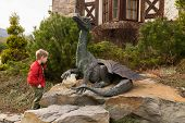 picture of alligator baby  - Little boy plays near a statue of a dragon - JPG