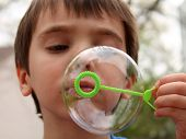 pic of blow-up  - Close up of ittle boy blowing bubbles outside - JPG