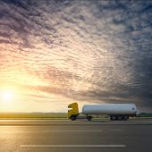 pic of tank truck  - Side view on tank truck in motion blur on highway towards the setting sun - JPG