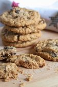 foto of baked raisin cookies  - Oatmeal raisin cookies on a table with a printed tea towel in the background - JPG