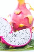 image of dragon fruit  - Dragon fruit on banana leaf against white background - JPG