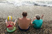 picture of scum  - grandfather with grandchildren sit on the beach and look at the sea - JPG