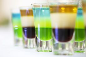 foto of shot glasses  - Colorful shot alcoholic cocktails green blue white brown and gold colours standing in a row on table top in glasses closeup of drinks background horizontal picture - JPG