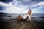Elegant lady with perfect body laying at the beach.
