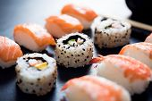 Close up of sushi served on black plate. Delicious japanese cuisine sushi prepared for one person. F poster