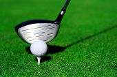 close up of a golf club, ball and tee on green grass