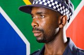 south african policeman portrait, background is south african flag