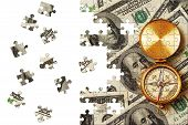 Puzzle Antique compass over 100 dollar bills background