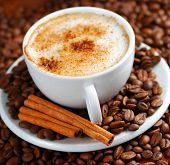 stock photo of cup coffee  - Cup of cappuccino  with cinnamon and spilled out coffee beans - JPG