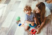 Mom playing with her son with toys on the warm clean floor at home poster