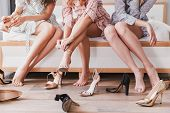 Cropped picture of attractive fashion girls 20s wearing dresses choosing and trying on summer stilet poster
