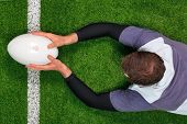 Overhead photo of a rugby player diving over the line to score a try with both hands holding the bal