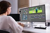 Young Female Editor Editing Video On Computer In Office poster