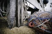 Close Up And Selective Focus Image. Wooden Cottage Pole And Fish Net On The Sandy Beach.blue Rope An poster