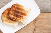 Scorched Toast In White Plate At Breakfast poster