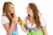 two bavarian girls with beer skoaling at each other