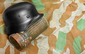 Germany retro helmet with metal bag for gas mask on a camouflage fabric.