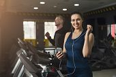 Young Woman With Smartphone Running On Treadmill In Gym. Slim Girl Jogging In Fitness Club, Listen M poster
