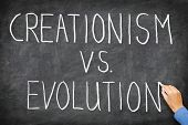 Creationism vs evolution. Religion and education concept. Hand writing on blackboard.