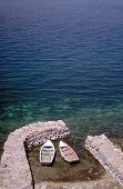 image of safe haven  - Two wooden boats moored in ancient stone harbour - JPG