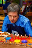 An Older Man With Down Syndrome Blows Out Candles On His Birthday Cake At A Pizza Party In His Honor poster