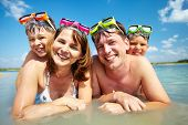 Photo of happy family looking at camera during summer vacation