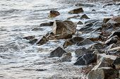The Sea Accumulates On The Coastal Rocks. Wave Nailed To The Shore. Large Rocks Near The Water. poster