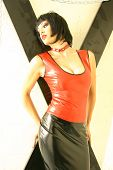 image of spanking  - Dominatrix in a latex outfit against back cross and silver chains - JPG