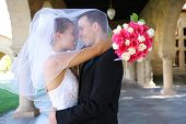 stock photo of wedding arch  - A beautiful bride and handsome groom at church during wedding - JPG